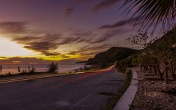 Car light trails during sunset at a coastline road in Corfu Greece . Royalty Free Stock Photo