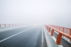 Car lights approaching foggy bridge Stock Images