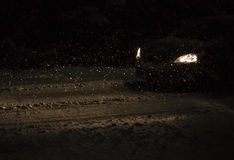 Car lights and falling snow.  Royalty Free Stock Photo