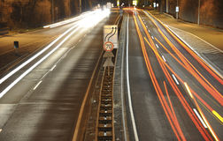 Car lights on german highway construction site with signs at night, long exposure photo of traffic. Car lights on a german highway construction site with signs Stock Photos