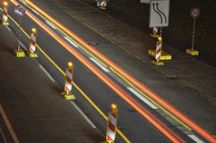 Car lights on german highway construction site with signs at night, long exposure photo of traffic. Car lights on a german highway construction site with signs Royalty Free Stock Photo
