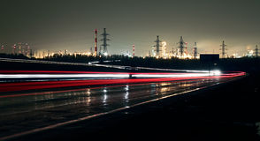 Car lights on a highway at night. On the background of the industrial landscape Royalty Free Stock Photography