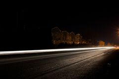 Car lights. Car light trails on road with old factory as background Stock Photo