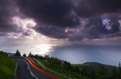 Car lights on the mountain road with clouds and sun over the sea at sunset, mount Jaizkibel stock photography