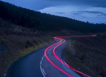 Car lights on mountain road at dusk. Jaizkibel, Basque Country, Spain Stock Photo