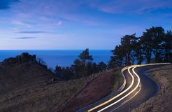 Car lights on the road of Mount Jaizkibel at sunset royalty free stock images
