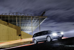 Family car at game stadium. A modern silver family estate car traveling at night in front of stadium with light trails royalty free stock photo