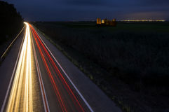 Car lights trails at night on the road towards the city Royalty Free Stock Images