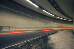 Car lights trails in a tunnel Stock Images