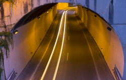 Car lights in a tunnel heading to the city Stock Images