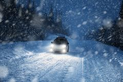 Car lights in winter forest. Travel by car to snow Stock Photo