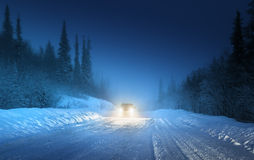 Car lights in winter forest Stock Images