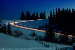 Car lights on winter snowy road. With snow-drafted firs on background Stock Photo