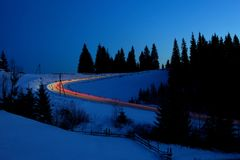 Car lights on winter snowy road. With snow-drafted firs on background Stock Images