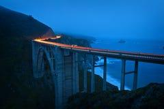 Car lighttrails at dusk on Bixby Bridge Stock Images
