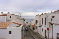 Car lined street in Lagos, Portugal with beach in background royalty free stock photo