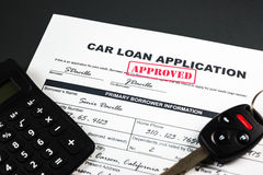 Car Loan Application Approved 001. Filled-up car loan application form with approved stamp, calculator and a remote car key royalty free stock photos