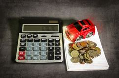 Car loan concept,saving money to buy car. Car loan concept, a calculator beside the red toy car and coins on a spiral notebook stock image
