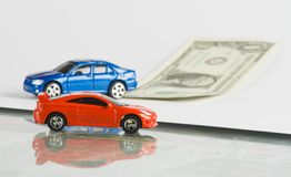 Car loan concept with toy cars and dollar bill. Finance stock images