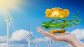 Car made of green leaf in gold piggy bank being cut in hand on wind turbine with blue sky background royalty free stock photo