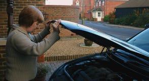Car maintenance female 2. Female undertaking car maintenance stock photography