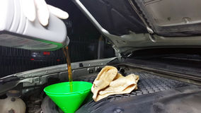 Car maintenance servicing mechanic pouring new oil lubricant into the car engine Royalty Free Stock Photo