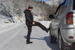 Car and man on snowy road. Human near broken car in winter Stock Images