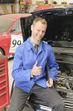 Car Masters, check everything is OK. Auto mechanic, mechatronic checked the engine compartment of a car in the garage, doing the 'thumbs up' gesture Stock Photography
