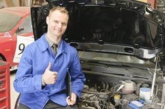 Car Masters, check everything is OK. Auto mechanic, mechatronic checked the engine compartment of a car in the garage, doing the 'thumbs up' gesture Stock Image