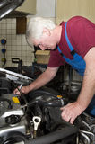 Car mechanic. A car mechanic servicing a vehicle stock image