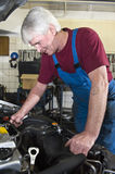 Car Mechanic. A senior motor mechanic servicing a car inside a garage royalty free stock images