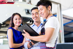 Car mechanic and Asian customer couple royalty free stock images