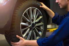 Car mechanic in workshop changing tires. Car mechanic in auto repair shop changing tires Royalty Free Stock Photos