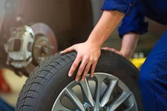 Car mechanic in workshop changing tires. Car mechanic in auto repair shop changing tires Royalty Free Stock Photography