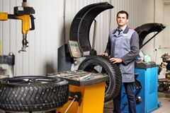 Car mechanic balancing car wheel on balancer in auto repair service. Professional car mechanic balancing car wheel on balancer in auto repair service Stock Photo