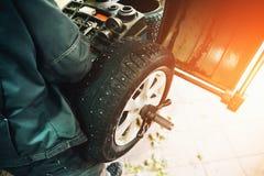 Car mechanic balancing car wheel on computer machine balancer in auto repair service Stock Photo