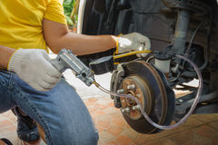Car mechanic bleed air out of brake system. DIY Stock Image
