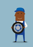 Car mechanic in blue uniform with wheel Stock Images