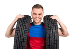 Car mechanic carrying two tires on white background. Royalty Free Stock Photos