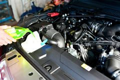 Car mechanic changes coolant on the vehicle. By mechanic in garage Royalty Free Stock Photography