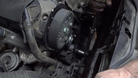 Car mechanic changing a rubber gear belt
