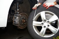 Car mechanic changing tire. Car mechanic changing tire in professional car repair service Royalty Free Stock Photos