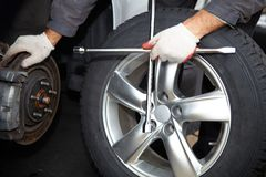 Car mechanic changing tire. Stock Photo