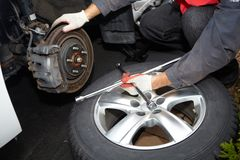 Car mechanic changing tire. Car mechanic changing tire in professional car repair service Stock Image