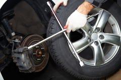 Car mechanic changing tire. Stock Photos