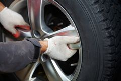 Car mechanic changing tire. Car mechanic changing tire in professional car repair service Royalty Free Stock Photography