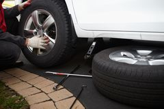 Car mechanic changing tire. Car mechanic changing tire in professional car repair service Royalty Free Stock Images