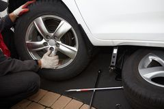 Car mechanic changing tire. Stock Photography