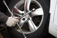 Car mechanic changing tire. Royalty Free Stock Image