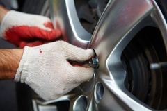 Car mechanic changing tire. Stock Photos